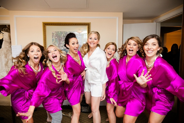 Bride in white robe with bridesmaids in bridal suite