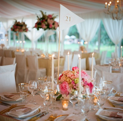 Gold-rimmed glassware inside tented reception