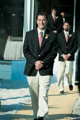 groomsmen walk down aisle wearing pink ties