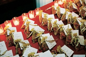 Gold organza wedding favor bags on candlelit table