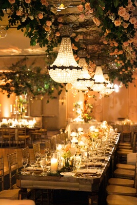 Long head table with low centerpieces and flower installation on ceiling