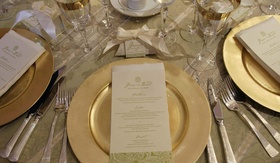 gold charger plate with white and green menu