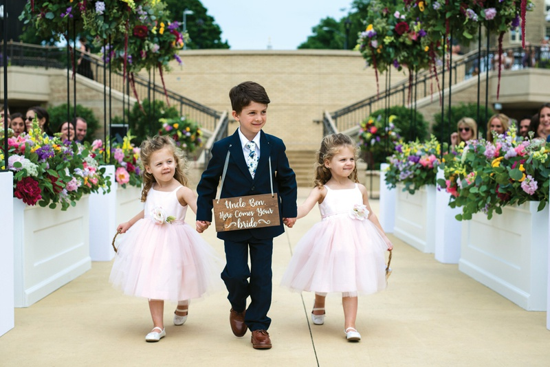 ring bearer with wooden sign around neck holds hands with two flower girls in blush dresses