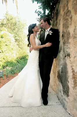 Bride in a Vera Wang gown and groom in a black tuxedo with an orchid boutonniere