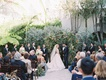 bride and groom under wood arbor greenery bistro lights guests in wood chairs white cushions