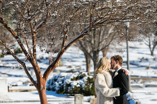 bride in fur coat kisses groom in tuxedo in the snow, winter wedding