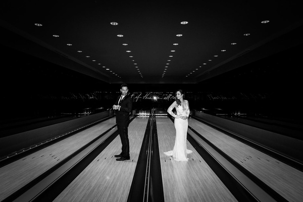 Black and white photo of bride and groom portrait in bowling alley on lanes unique wedding pic idea