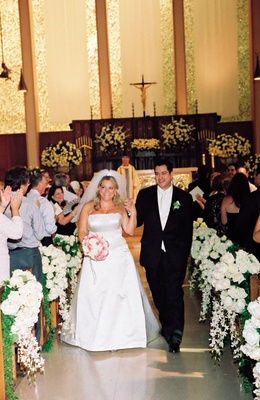 Bride and groom walk up ceremony aisle decorated with white flowers