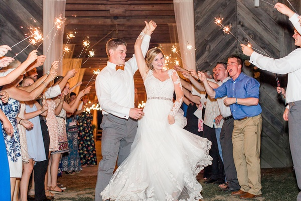 Bride in wedding dress illusion long sleeves dancing twirl in tunnel of sparklers wedding exit