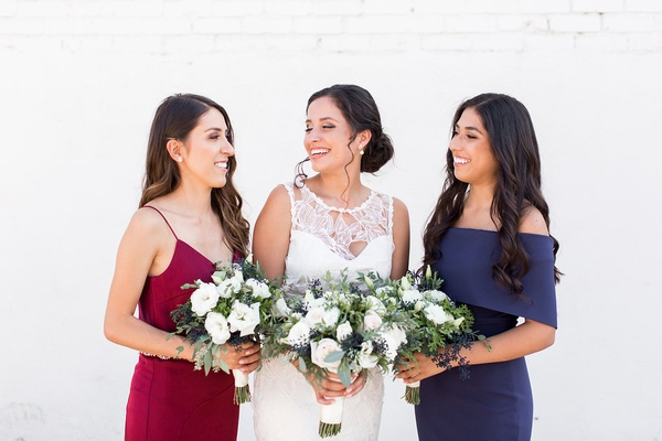 Bride in Claire Pettibone dress with bridesmaids in navy and oxblood red dresses mismatched styles