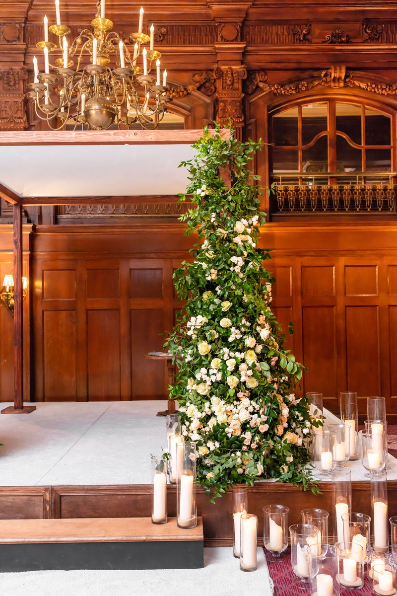 wedding ceremony decor stage with pillar candle in hurricane vases greenery arbor with white flowers