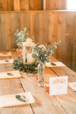 Rustic wedding reception low DIY centerpieces lantern eucalyptus greenery napkin green leaf escort