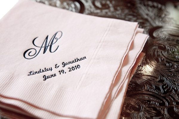 Pink beverage napkin with black names and monogram
