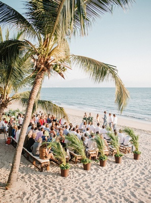 Wedding ceremony on sand beach in Mexico ocean view palm trees palm plants benches intimate wedding