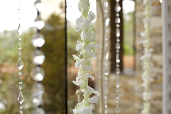 Crystal bead strands and white orchid leis against window