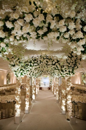 Ballroom ceremony with white roses and greenery decorations