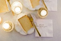 wedding cake slice on white plate gold fork personalized napkin candle votives