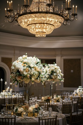 Tall centerpieces white and peach blush flowers round arrangement crystal chandelier round tables