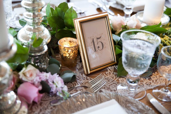 A simple tablescape inspired Secret Garden with leafy table runner and gold frame table number