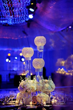 White flowers at base of crystal orbs on glass vases