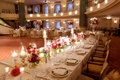 Long wedding reception table with candles, low flower arrangements, gold details by dance floor
