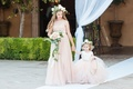 Flower girls in champagne tulle dresses with bouquet and flower crowns walking down white aisle