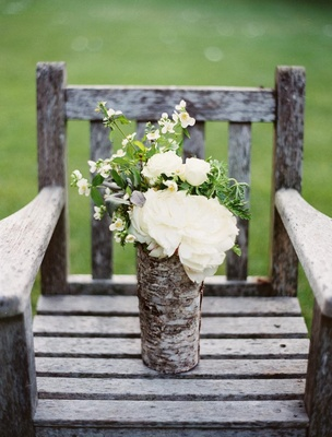 Wedding arrangement of white flowers in a vase wrapped with birch wood