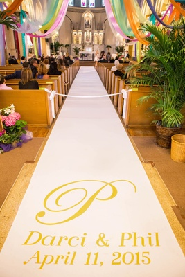 Personalized monogram aisle runner with names and wedding date and colorful drapery over church pews