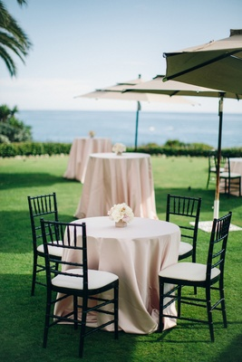 Pink cocktail tables on grass lawn with ocean view