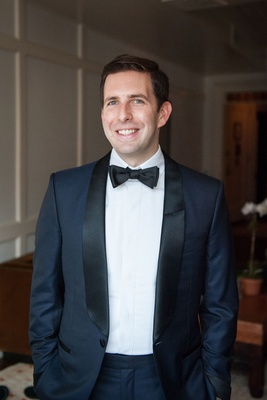 Wedding attire for groom navy blue tuxedo jacket with black lapels and bow tie