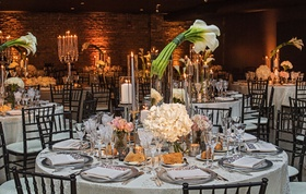 wedding reception brick wall round table calla lily flower centerpiece glass hurricane hydrangea