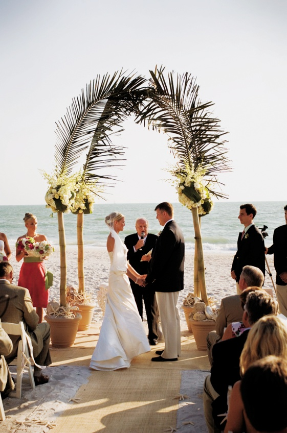 ceremony arch made of bamboo, flowers, and palm fronds