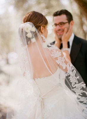Bride touches groom's cheek with lace bridal veil
