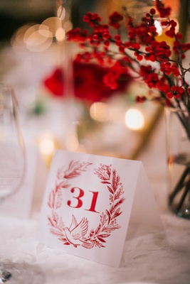 wedding reception holiday theme red wreath dove table number on white linen red foliage winter