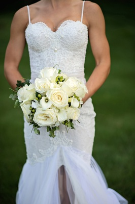 Bride in a Berta Bridal gown holds bouquet of white roses and calla lilies, greenery