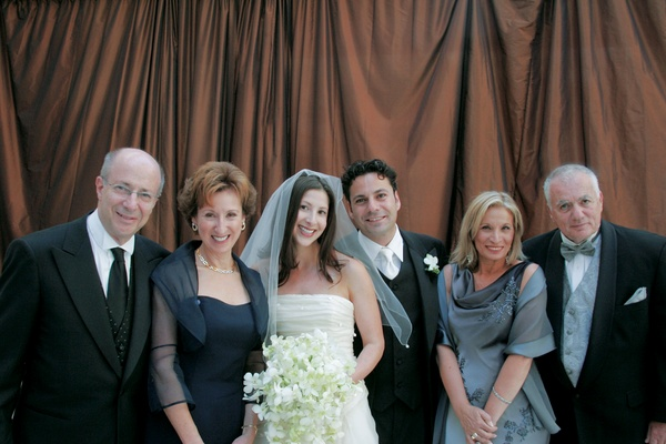 Bride and groom with both sets of parents standing in front of brown draping