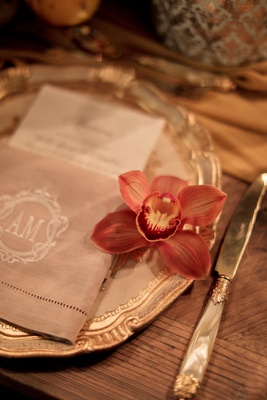 blood orange orchid on the side of napkin and menu on charger plate