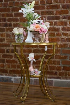 white lilies, white anemone, small pink roses, peach roses, orchids, gold table