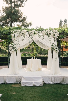 White drapery wedding ceremony structure chuppah ivory flowers greenery white stage grass lawn