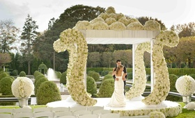White chuppah with ivory flowers and hydrangeas