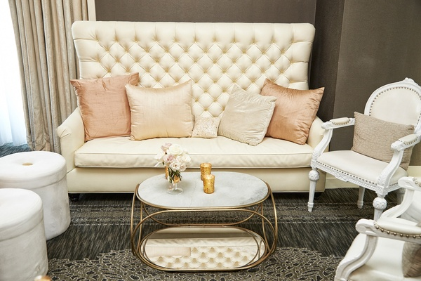Reception seating area with a tufted high-backed couch, pink pillows, and white chairs