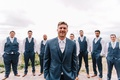 Groom and groomsmen in 3 piece navy blue suits