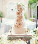Wedding cake surrounded by white flower petals and sugar flower decorations mercury glass candles