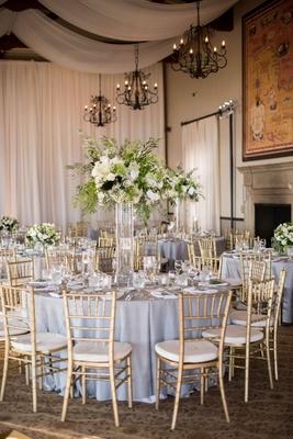 gold chiavari chairs, lucite vessel holding green and white flower arrangement