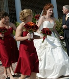 Bride in white ball gown with bridesmaids in short red dresses