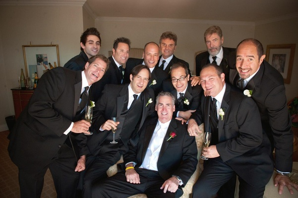 Men in tuxedos with champagne in suite