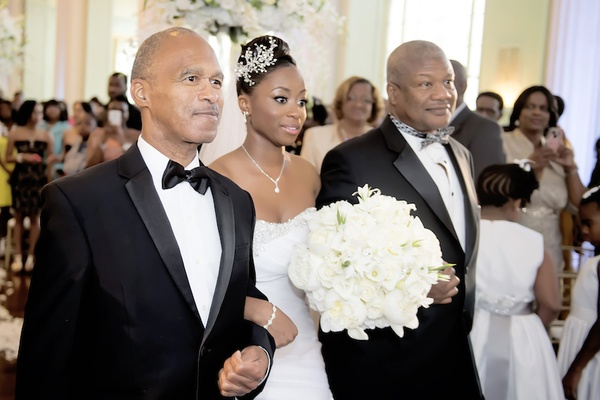 African American bride with headpiece walks down aisle with two dads