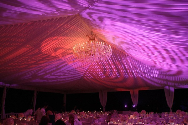 Tented wedding reception with colorful amber and violet lighting and a Maria Theresa chandelier