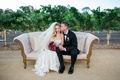 bride and groom sit on white and gold couch on vineyard with red and purple bouquet