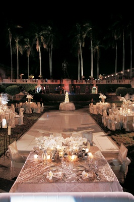 Outdoor evening reception with white dance floor and ivory tables